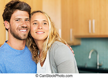 Young couple at home in the kitchen - Happy young couple at...