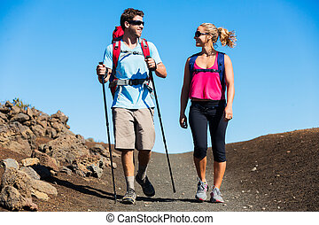 Hiking in the mountains. Athletic couple with backpacks...