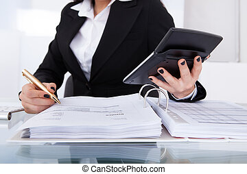 Accountant Calculating Tax - Midsection of female accountant...