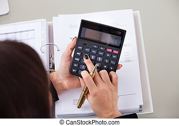 Accountant Calculating Tax At Desk - High angle view of...
