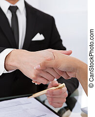 Business Colleagues Shaking Hands - Cropped image of...