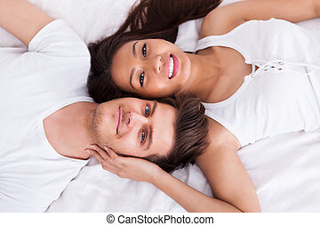 Young Couple Lying On Mattress - Directly above shot of...