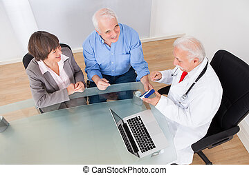 Senior Couple Discussing Over Medicine - High angle view of...