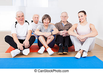 Female Trainer With Senior Customers At Gym - Portrait of...