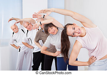 Trainer And Customers Doing Stretching Exercise - Full...