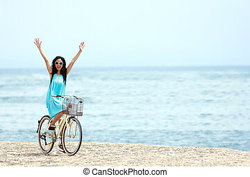 woman having fun riding bicycle at the beach
