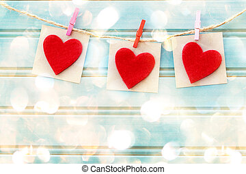 Hand-crafted felt hearts hanging with clothespins over shiny...