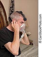 Sleep Apnea - Man wearing his CPAP machine before sleeping
