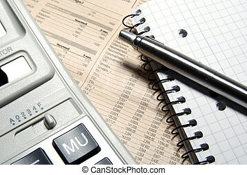 Financial calculator, steel pen and notebook laying on newspaper. Concept.