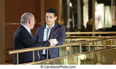 Coffee-Break Chat - Two men talking in business centre hall,...
