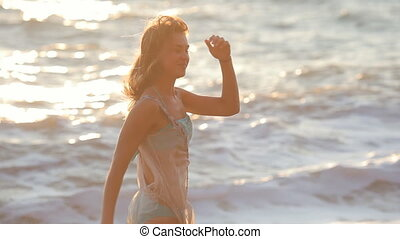 Happy girl runs along the beach and swirls - Carefree woman...