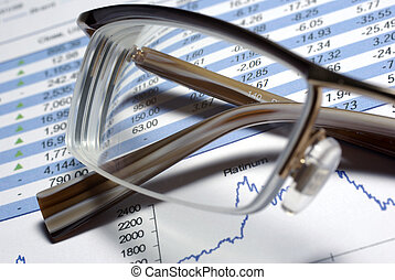 Glasses laying on printed financial report Some graphs and...