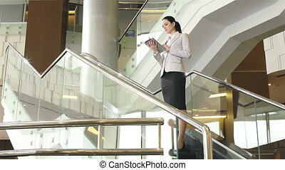 Business Today - Dolly of business lady standing on stairs...