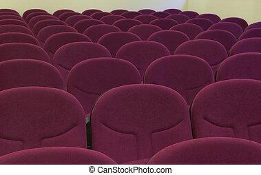 Cinema interior with comfortable red chairs.