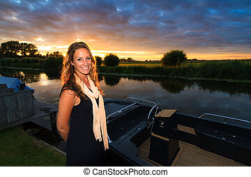 Sunset sloop woman - Beautiful woman standing next to a...