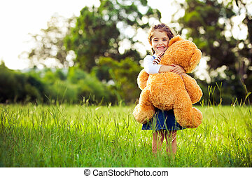 Little cute girl standing in the grass holding teddy bear -...