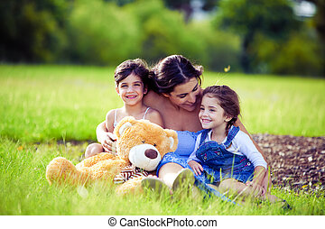 Mother and two daughters playing in grass