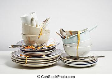 Dirty dishes pile needing washing up on white background -...