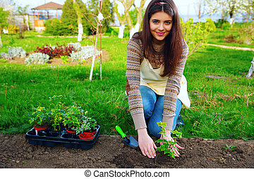 Smiling woman planting flowers in the garden