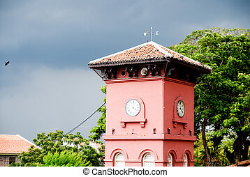 red clock tower in cloudy weather with surrounding trees