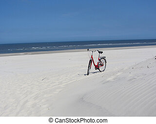 red bicycle in bright sand
