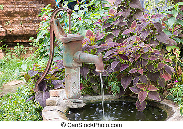 water pump - An old fashioned hand water pump above old...