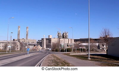 Close up view of the cement factory with some smoke getting...