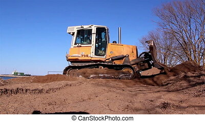 A yellow bulldozer moving the soil