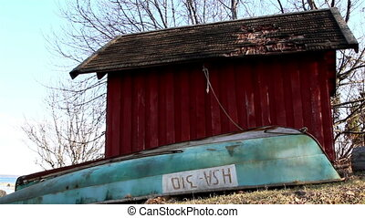 The red little house with an unused boat beside it and some...