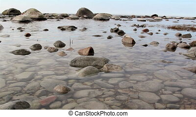 The tranquil view of the sea with lots of rocks on it