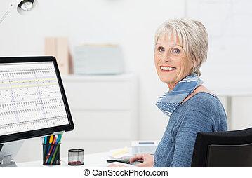 Beautiful elderly businesswoman sitting at her desk working...