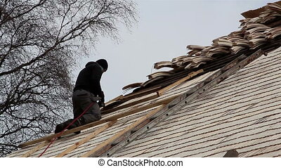 A roofer nailing some wooden shingles on the roof of the...