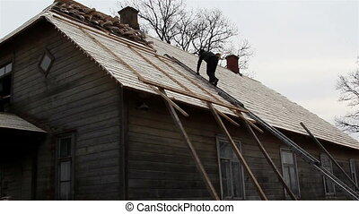 A roofer climbing on the roof using the ladder to put some...