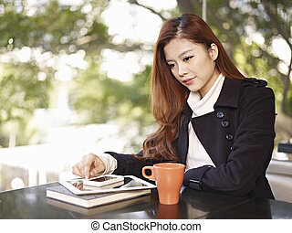 young woman thinking in coffee shop - young asian adult...