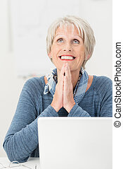 Happy elderly woman giving thanks to heaven sitting looking...