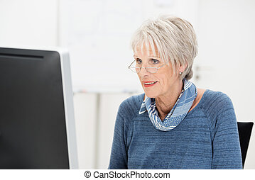 Senior businesswoman wearing glasses working at her desk...