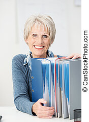 Happy contented senior businesswoman holding onto a row of...