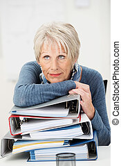 Overworked elderly businesswoman resting her chin on top of...