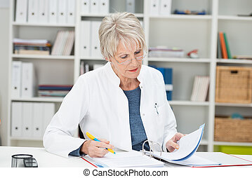 Elderly businesswoman working at her desk at the office...