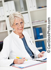 Happy confident senior businesswoman sitting working on...