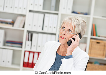 Elderly businesswoman listening to a call on her mobile...