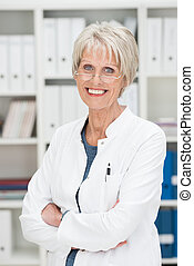 Smiling successful senior businesswoman standing with folded...