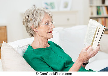 Attractive elderly woman reading at home - Attractive...