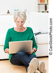 Senior woman relaxing at home with a laptop computer sitting...