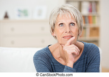 Wistful senior woman sitting thinking staring pensively up...