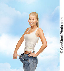 sporty woman showing big pants - fitness, diet and...