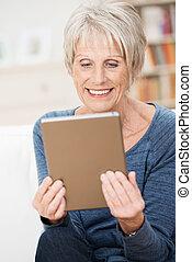 Attractive senior woman enjoying an e-book smiling as she...