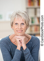Attractive elderly blue-eyed woman sitting looking directly...