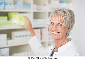 Smiling happy female pharmacist reaching for medication on...