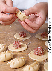 Cook hands preparing Asian gyoza dumplings with minced meat...
